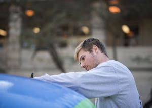 Joe Krahulik, senior, signs the free speech ball outside Ballantine Thursday. Young Americans for Liberty asked people to write whatever they wanted on the giant beach ball in the spirit of free speech.
