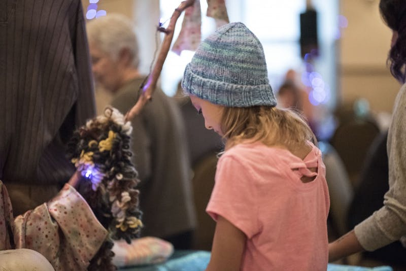 Chloe Senior, 11, looks at hats at Wrapped in Love in the Fountain Square Ballroom on Sunday. The event benefitted Middle Way House, and each attendee was able to choose one hat for participating in the event.
