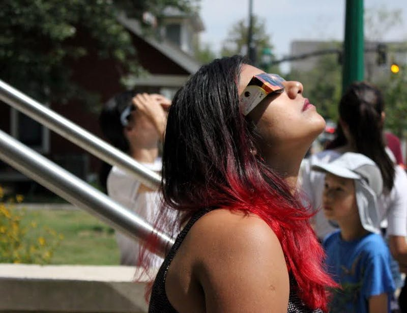Risana Malik, a second-year graduate student and an assistant at the Asian Culture Center, gazes into the sky as the sun crosses the moon. The last total solar eclipse to pass through the contiguous United States was in 1979.