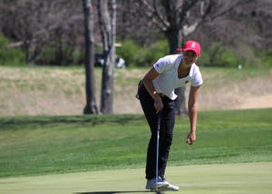 Freshman Emma Fisher picks her ball out of the hole after sinking a putt on April 8, 2017, during the IU Invitational at the IU Golf Course.