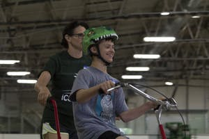 Jake Halvorson (right) rides alongside his mother, Lisa Halvorson (left), at the iCan Bike Camp on Thursday, May 17, in the Frank Southern Ice Arena. The camp teaches confidence and bike riding to people with disabilities.