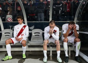 From left, freshman midfielder Justin Rennicks, junior defender Andrew Gutman and junior midfielder Jack Griffith sit on the bench while the NCAA Championship trophy is presented to Stanford after IU lost 1-0 to Stanford in overtime on Dec.10 in Chester, Pennsylvania. Stanford scored a goal in the 103rd minute of the game.