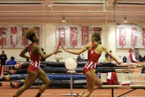 Junior sprinter Jaela Gay hands off the baton in third lap of the 4x400-meter dash to sophomore distance runner Mallory Mulzer. The 4x400 team came in third place in the race at the 2018 Hoosier Hills meet.