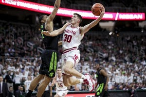 Forward Collin Hartman attempts a layup while charging the basket during the Hoosiers' game against the Michigan State Spartans on Friday at The Breslin Center in East Lansing, Michigan. The Hoosiers fell to the Spartans, 85-57.