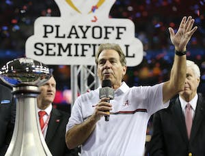 Alabama head Coach Nick Saban is presented the trophy after a 24-7 victory against Washington in the Peach Bowl at the Georgia Dome in Atlanta on Saturday, Dec. 31, 2016. Saban won his sixth national championship against Georgia Monday night.