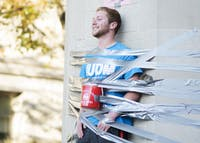 Isaac Peasley, a junior, tapes himself to the Sample Gates for IU Dance Marathon's Day of Hope. Peasely, who has participated in six dance marathons, said he started getting involved with the event when a close friend received medical treatment from Riley Hospital for Children in Indianapolis.