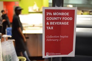 A sign hangs on the cash register of The Round café in Forest Residence Center informs students of the new Monroe County food and beverage tax. The 1-percent tax will not apply to food courts or stores on the IU campus for current students.