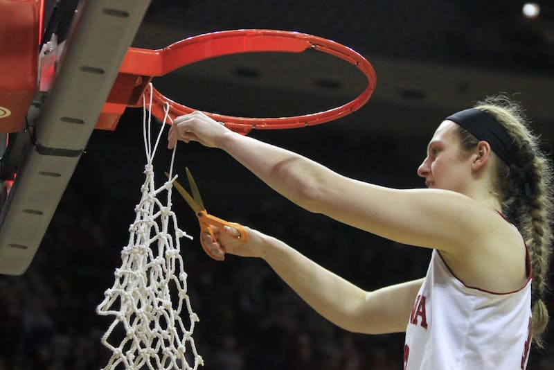 Senior forward Amanda Cahill cuts one of the final threads of the net. Cahill and fellow senior Tyra Buss ended their college basketball careers Saturday, March 31, with a win against Virginia Tech, 65-57.