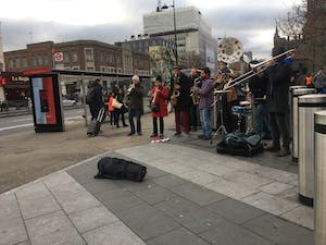 A group of seven musicians stands outside the King's Cross tube station playing instruments. The group is one of many that can be seen on the streets of London.