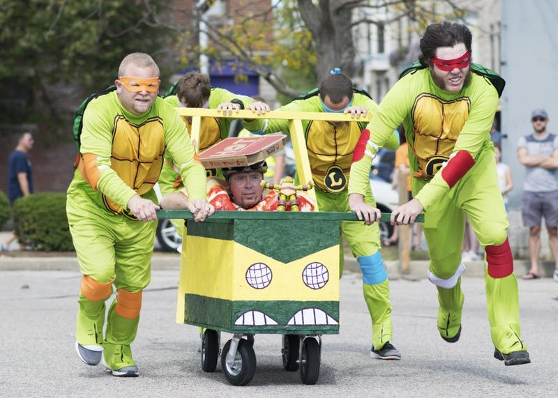 Team Turtle Power hurtles around the corner of the track during the final round of coffin races at the Updraft & Campus Costume Coffin Races on Oct. 7. Turtle Power tied for first place with a time of 33.5 seconds before being voted the overall winner by applause from the audience.