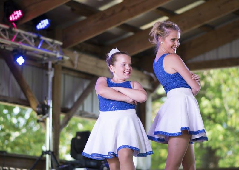 Chloe Wirt, 9, and Maddie Wright, a senior at IU, dance at the Monroe County Fall Festival on Sept. 23 with Indiana Dance Company. The dancers performed multiple clogging styles of dance.