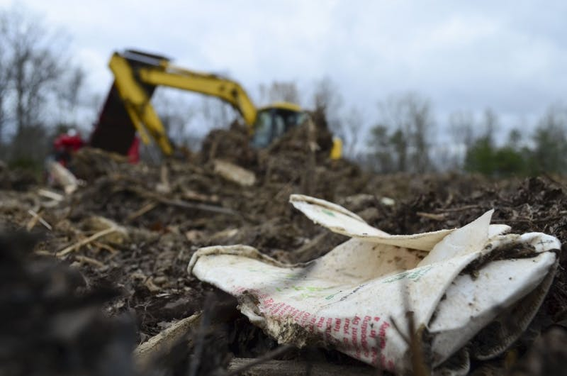 A compostable Coca-Cola cup lies in the compost yard at Green Earth. Each week, IU brings 10,000 pounds of compostable waste here to be composted.