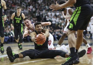 Michigan State junior forward Kenny Goins takes possession from Indiana junior guard Zach McRoberts during the Hoosiers' game against the Michigan State Spartans on Friday at The Breslin Center in East Lansing, Michigan. The Hoosiers fell to the Spartans, 85-57.