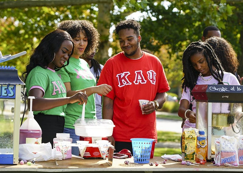 IU National Pan-Hellenic Council members make popcorn and snow cones during the NPHC fair held Saturday afternoon in Dunn Meadow. Members from various NPHC chapters came together to celebrate and reach new students interested in joining greek life.