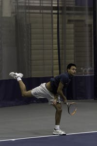 ACES HIGH: Rohan Vohra '21 kicks his leg up high after serving the ball to his opponent during a match on March 9.