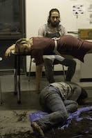 MÉNAGE À TROIS: A dead Mae (Sophia Massidda '20) lies on the table between Lloyd (Yair Koas '19, seated) and Henry (Zoë Rose '20, floor).