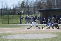 BOMBS AWAY: Max Hart '16 swings through an NYU pitch and puts the ball in play during a game on April 17th, 2016.
