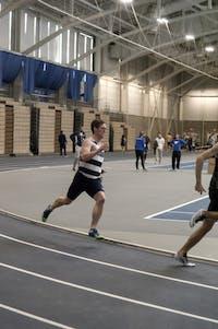 ROUNDING THE CORNER: Sprinter Adam Beckwith '18 runs hard at last year's Reggie Poyau Invitational on Jan. 14, 2017.