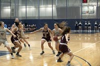 HART DRIVE: Guard Eva Hart '18 splits the Chicago defenders on her way to the basket during the game on Feb. 11.