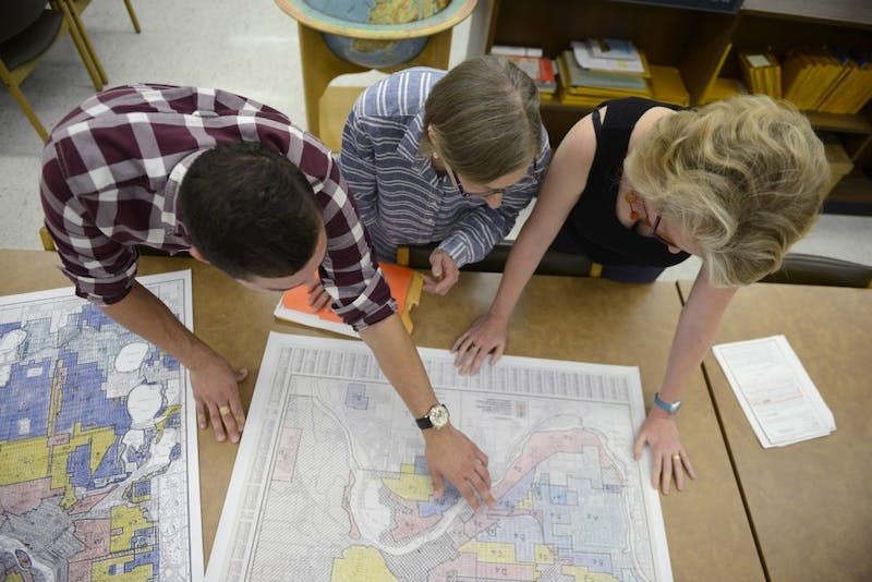 "Kevin Ehrman-Solberg, Kirsten Delegard, and Penny Peterson look at city maps that show segregated areas in the metro area at Wilson Library on West Bank on Wednesday August 30, 2017. ""People like to believe Minneapolis had neither race nor racism,"" Delegated says."