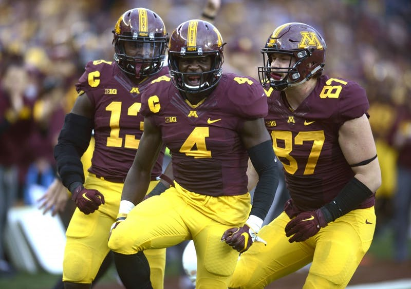 Defensive back Adekunle Ayinde celebrates with his teammates after a sack against Illinois at TCF Bank Stadium during the Homecoming game on Saturday, Oct. 21.
