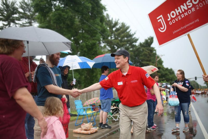 GOP-endorsed candidate for Minnesota Governor Jeff Johnson shakes hands with parade spectators at the Father Hennepin Parade in Champlin, Minnesota on Saturday, June 9.