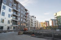 Construction workers continue work Monday on the unfinished Prime Place Apartments where some residents have already moved in.