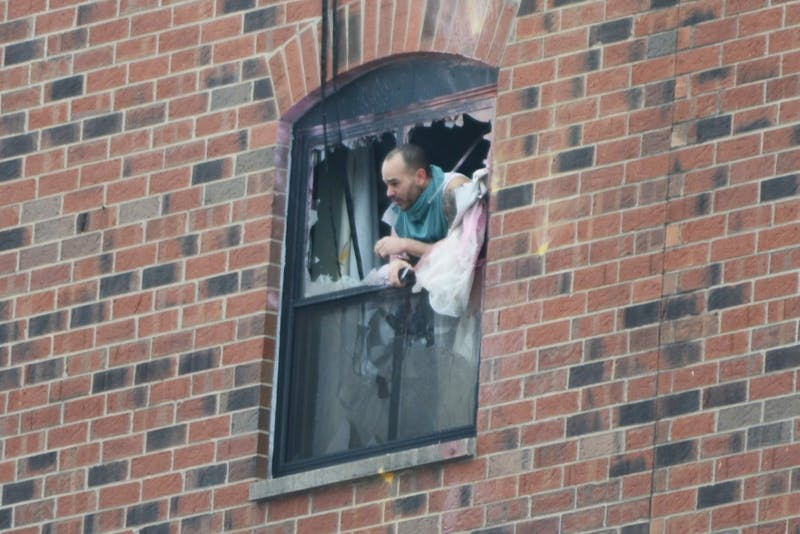 A man pokes his head out the sixth floor window at 11:40 a.m. after police fired gas into a sixth floor room at the Graduate Hotel. Police say the suspect is in the room and believe he is the only person in the room.