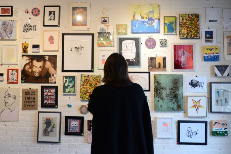 Stacy Dennis views artwork in search of holiday gifts at the Soo Visual Arts Center in Uptown.