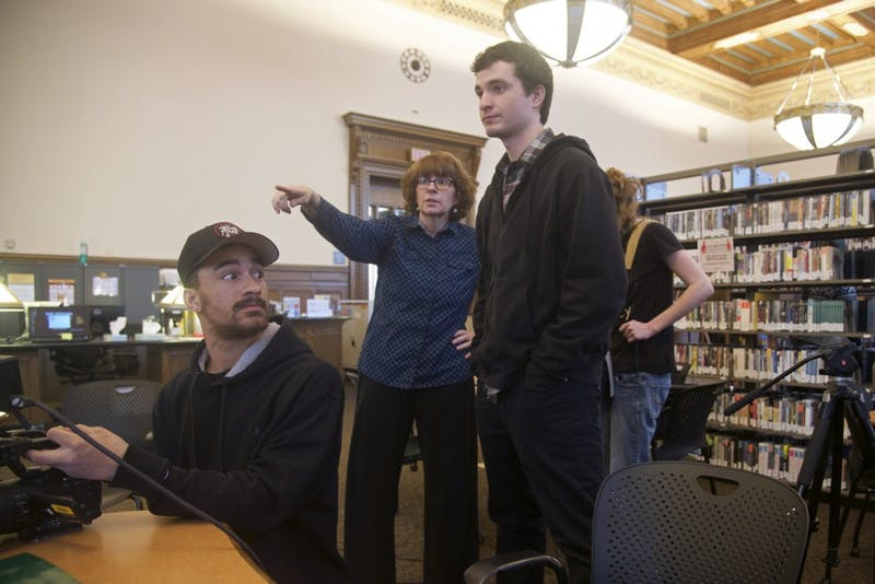 Junior Forrest Casey considers actors' positioning while filming an anti-theft PSA in Walter Library on Saturday, April 21.