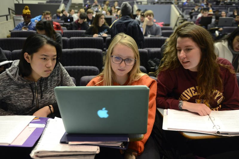 Lauren Kalvin, right, Emma Dombrow, center, and Pakou Lee, left, work together on a class activity during Biology 1001 on Tuesday Nov. 21 in Willey Hall on West Bank.