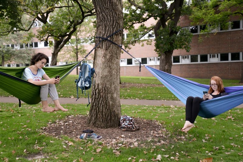 Students pose for a photo while using their phones to browse the internet via eduroam, the University's updated internet service, while lounging in hammocks outside Frontier Hall on Sept. 1, 2017.