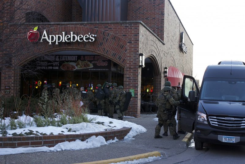 """SWAT personnel gather outside the Graduate Hotel early Monday morning in response to what the University is calling a """"public safety situation"""" involving someone inside the hotel."""