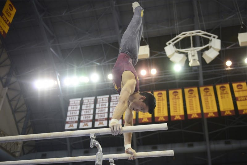 Justin Karstadt competes on the parallel bars against Penn State at the Sports Pavilion on Jan. 23, 2016.