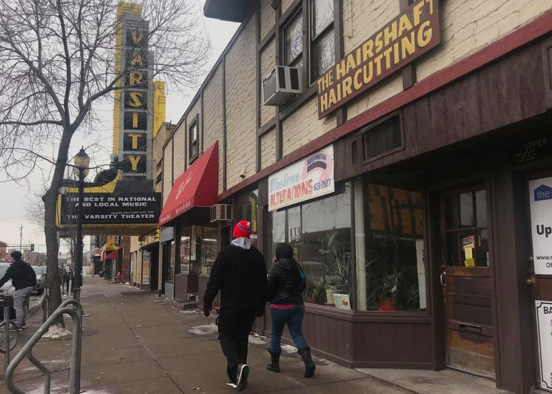 People walk past businesses on 4th Street Southeast in Dinkytown on Sunday, Feb. 18. A group of businesses are being forced to close after the building's owner decided to sell the property.