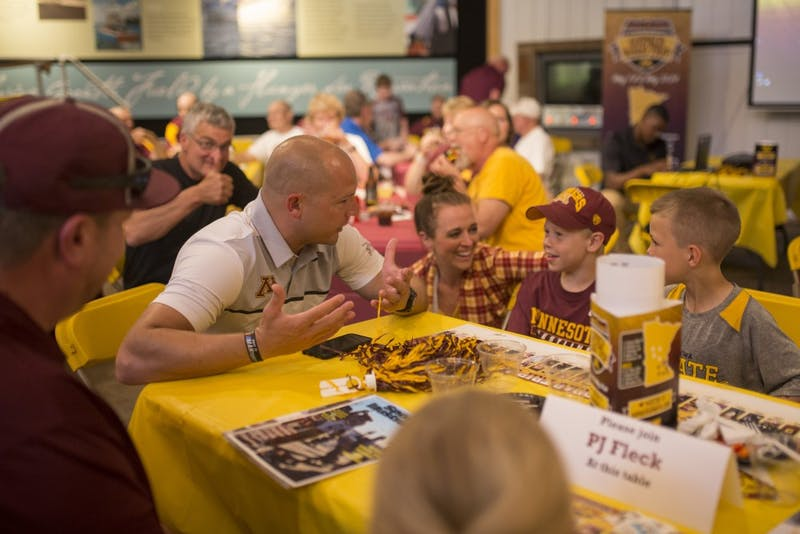 P.J. Fleck converses with Macaille Mahoney Hafner, left,Fynn Bakke and Henry Mayer at Fleck's table during the Gopher Road Trip at the Legacy of the Lakes Museum on Thursday, May 24 2018 in Alexandria, Minnesota.