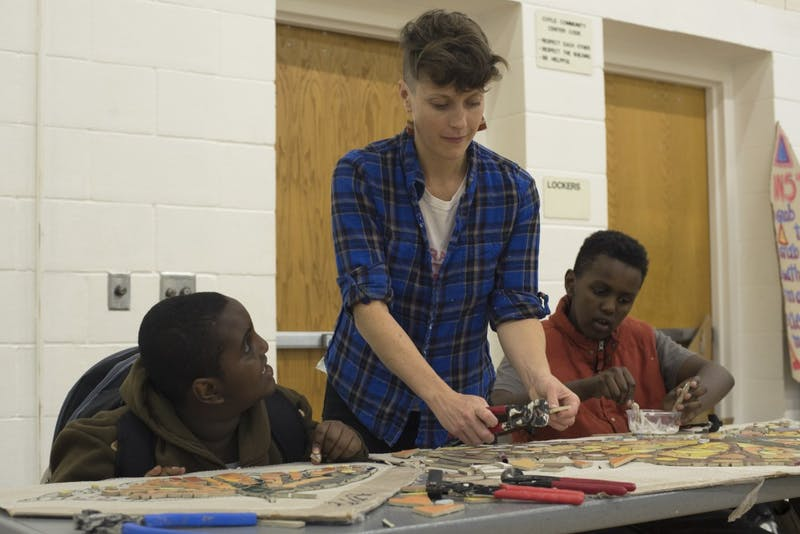 Jacqui Rosenbush of GoodSpace Murals makes mosaics with children from the Cedar-Riverside neighborhood Abdi Qabar, left, and Faisal Mohamed at the Brian Coyle Center Wednesday.