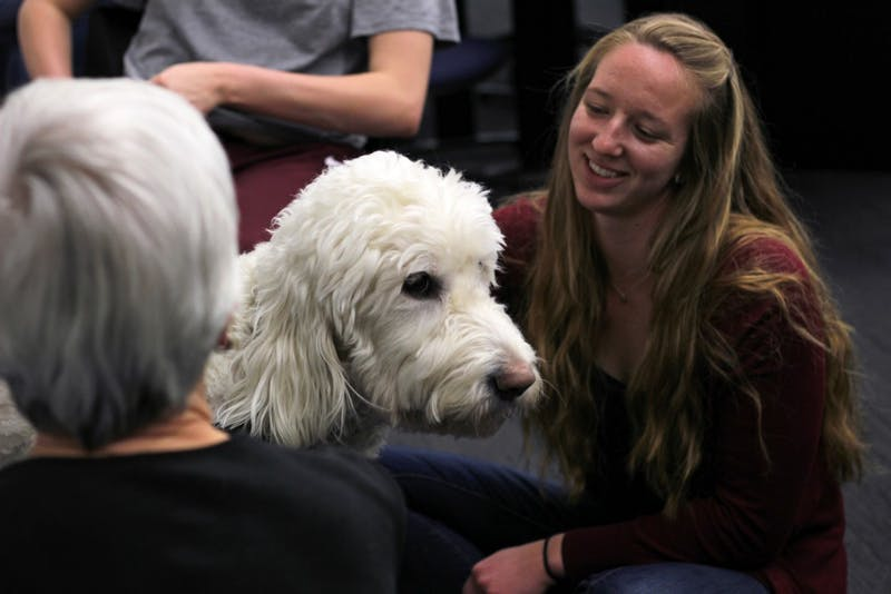 Junior Melissa Foster interacts with the dogs brought in from PAWS before her test in BIOL 1003 on Monday, April 2. She said that the dogs helped reduce her stress.
