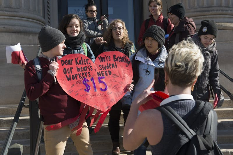 Members of the 15 for Student Workers group sing outside of Morril Hall on Wednesday, Feb. 14. Two students were eventually let in to deliver the large valentine card the group the created to University President Eric Kaler.