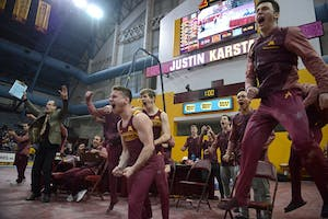 Teammates cheer for Justin Karstadt after sticking his landing on the pommel horse during a meet at Maturi Pavilion on Sunday, March 18.