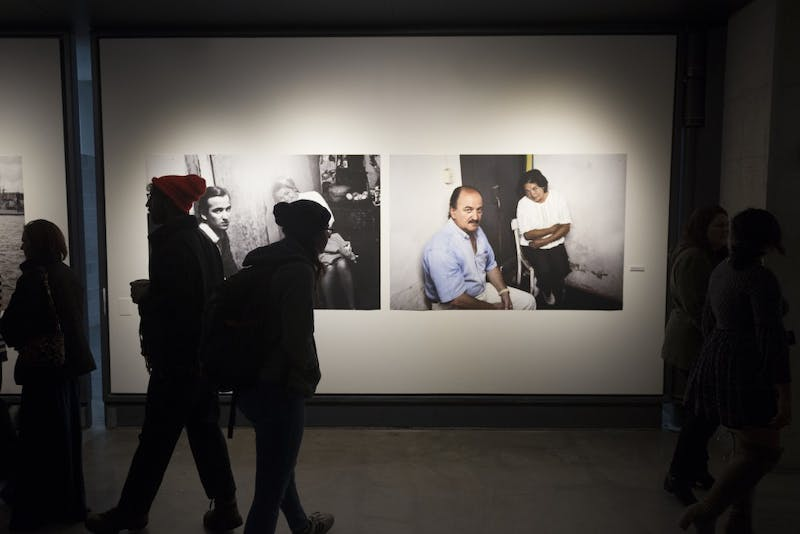 """Viewers of Gustavo Germano's work roam the gallery at the exhibit opening at Regis East on West Bank on Friday, Nov. 10. Germano's exhibition entitled """"Absences"""" showcases people detained or murdered by civic-military dictatorships in Argentina, Uruguay and Brazil."""