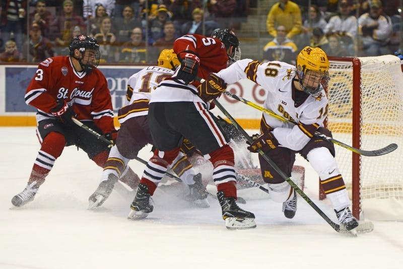Gophers forward Leon Bristedt assists forward Taylor Cammarata with his first period goal against St. Cloud State at 3M Arena at Mariucci on Oct. 21, 2016.