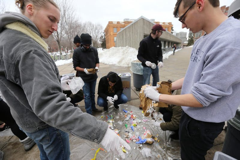 Environmental science policy management senior Eli Miller and strategic communications sophomore Jacob Van Blarcom sift trash from the Coffman Marketplace food court that wasn't already tossed into the correct recycling, compost or waste bin on Wednesday, April 18 outside Williamson Hall.