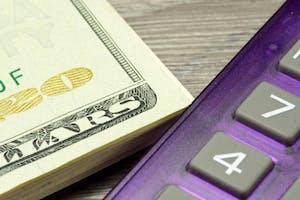 Viele Dollar Geldscheine und ein Taschenrechner