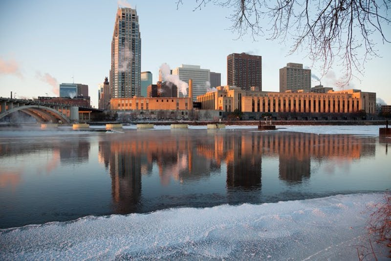 Downtown Minneapolis skyline across from the Mississippi River in the morning sun during the winter.