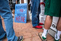 A sign made by the OU College Democrats encourages students to register to vote outside Baker Center on Oct. 1. The OU College Democrats and the OU College Republicans actively tabled and held events leading up to the election in November. (FILE)