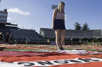 Lydia Ramlo, a junior at Ohio University, looks at a quilt at the Monument Quilt, a public healing space for survivors of sexual assault. The quilt was displayed at Peden stadium on Friday, October 13.