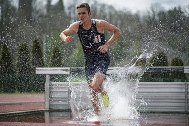 Cameron Kinsey trudges through water during the 3000 meter steeplechase at Ohio Track and Field's Cherry Blossom Invitational on April 7. (BLAKE NISSEN   FILE)