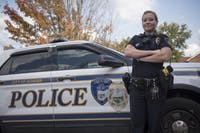 Officer Amelia Jenne poses next to an Athens Police Department car. (FILE)