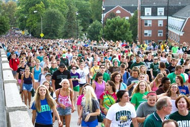 Thousands of freshman students follow the Marching 110 across the Richland bridge on their way through the involvement fair on August 24, 2014. (File)